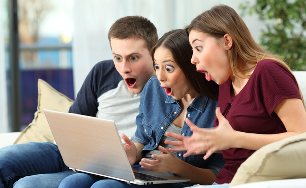 group of adults looking surprised at a laptop